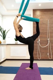 Женщина делает муху йоги, растяжения стоя на одной ноге на земле и второй в гамаке
