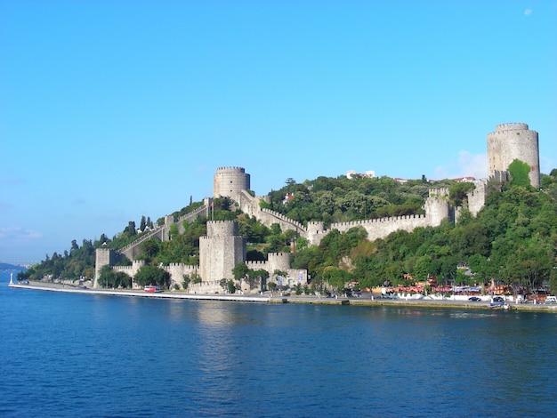 Форт с двумя башнями и оборонительной стеной на острове в море.
