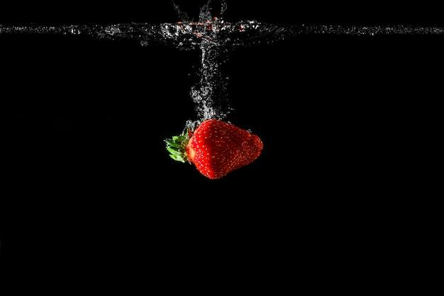 黒い背景と水のイチゴ。