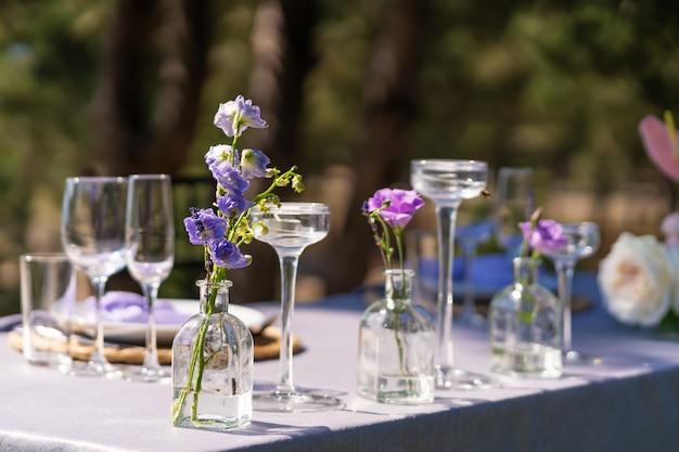 お祝いテーブルの装飾的な装飾。ガラスの花瓶と生花。戸外での休日の装飾