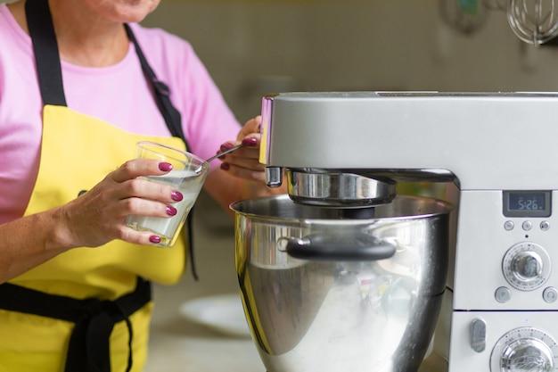 Женщина профессиональный кондитер готовит десерт. добавляет ингредиенты и перемешивает тесто в миксере.