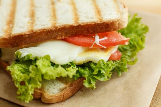 グリルの後、ベーコン、新鮮な野菜、グリーンサラダ、濃い線でジューシーなサンドイッチをクローズアップ。