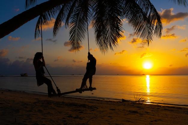 愛のシルエットカップルは日没時にビーチを散歩します。ヤシの木に縛られたブランコに乗って、太陽が海に沈むのを見る