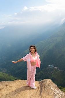Девушка наслаждается видом на горы, стоя на скале