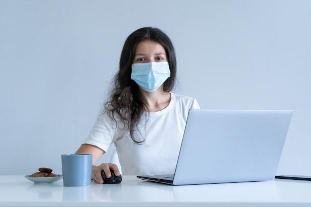 Девушка работает из дома во время карантина. коронавирус пандемия. девушка в хирургической маске работает на ноутбуке и пьет кофе. удаленная работа