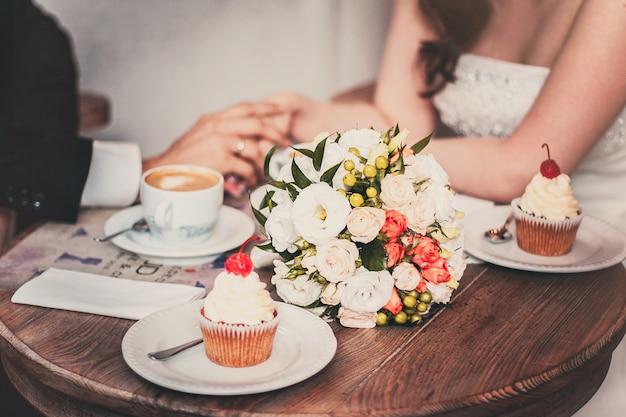 愛するカップルは結婚式の後にコーヒーを飲みます。新婚夫婦の手
