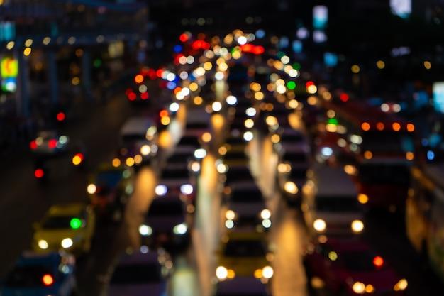 ぼやけた映像。広い通りの渋滞。ぼやけたブレーキライト。密集した都市交通。トランスポートインターチェンジ。夜の映像。