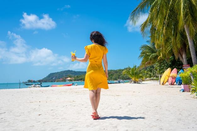 Красивая девушка в желтом платье пьет свежее манго на пляже райского острова. идеальный отпуск.