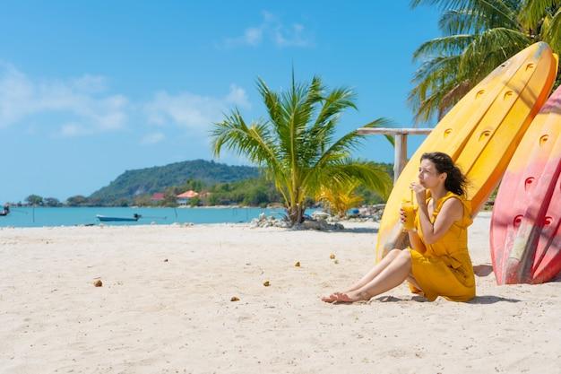 Девушка в желтом платье на тропическом песчаном пляже работает на ноутбуке возле каяков и пьет свежий манго. удаленная работа, успешный внештатный сотрудник. работает в отпуске.