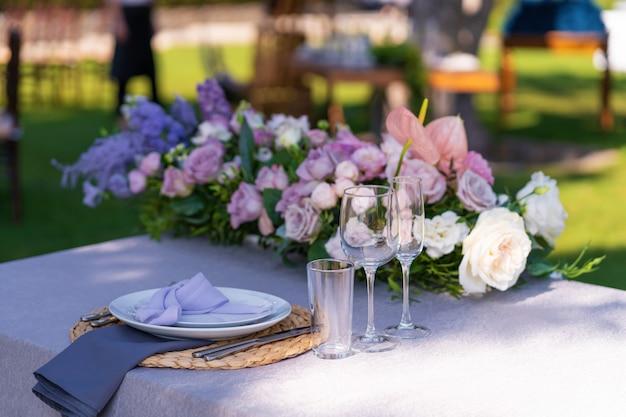 Декоративное украшение праздничного стола. стеклянные вазы и свежие цветы. оформление праздников на открытом воздухе