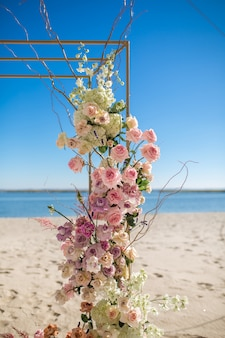 Часть свадебной арки, украшенная живыми цветами, установлена на голубом небе.
