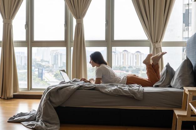 美しい若いブルネットの少女は、高層階からの美しい景色を望むパノラマの窓のそばのベッドに横たわっている間、ラップトップに取り組んでいます。スタイリッシュでモダンなインテリア。居心地の良い職場。