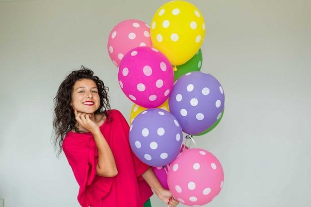 色の風船を持つ美しいかわいい陽気な女の子