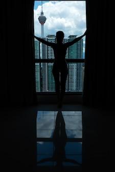 Стройная девушка смотрит на город через большое окно. верхний этаж.