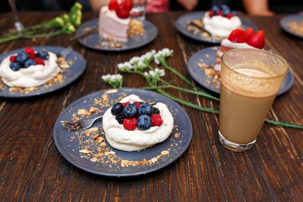 Сладкие пироги с летними ягодами на деревянном столе. вечеринка, сладкий столик. летнее предложение десертов в ресторане.
