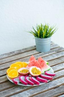 スライスされたフルーツの白いプレート。新鮮な果物とビタミン。静物色の夏の果物。