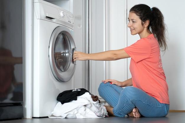 Девушка загружает грязное белье в стиральную машину, сидя на полу в квартире. прачечная день, работа по дому