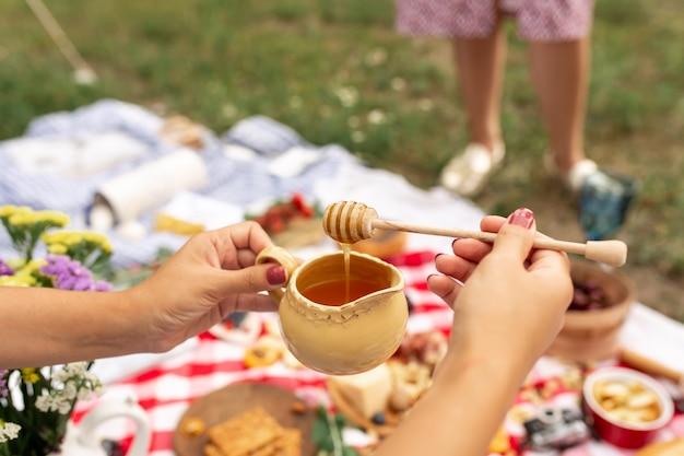 女性は木製の蜂蜜スプーンを持ち、蜂蜜はそれからポットに滴り落ちます。