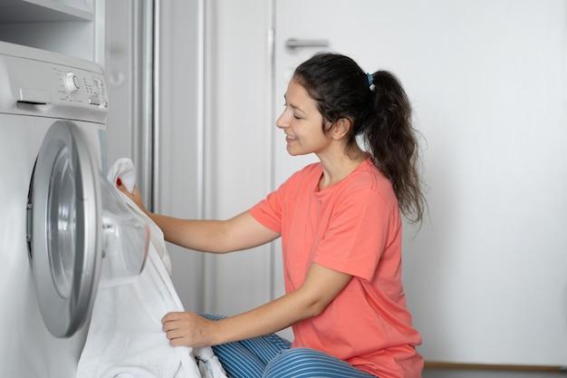 女の子がアパートの床に座っている間に汚れた洗濯物を洗濯機に入れます。洗濯日、家事