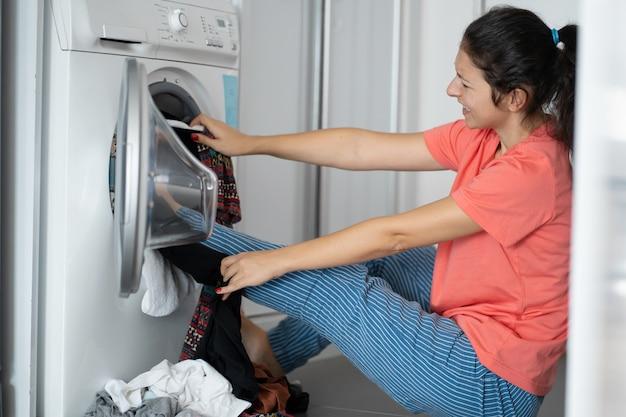 Девушка пинает грязное белье в стиральной машине. много грязной одежды, которая не помещается в стиральную машину. прачечная день, работа по дому