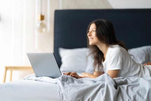 Красивая молодая брюнетка девушка с ноутбуком, лежа на кровати. стильный современный интерьер. уютное рабочее место. покупки в интернете.