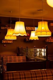 カフェの居心地の良いインテリア。暖かい黄色のライトシャンデリアと市松模様のソファ