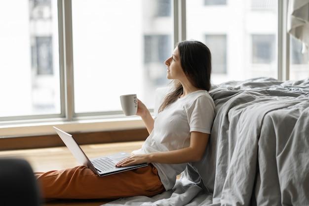 Красивая молодая брюнетка девушка работает на ноутбуке и пить кофе, сидя на полу возле кровати у панорамного окна. стильный современный интерьер. уютное рабочее место. покупки в интернете.