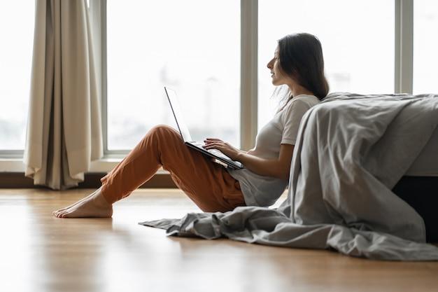 Красивая молодая брюнетка девушка работает на ноутбуке, сидя на полу возле кровати у панорамного окна. стильный современный интерьер. уютное рабочее место. покупки в интернете.