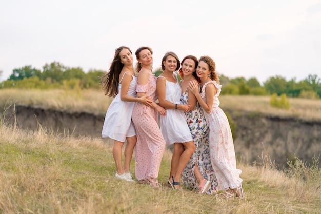 美しい女の子の友人の陽気な会社は会社を楽しみ、緑の丘の美しい場所で一緒に楽しみます。