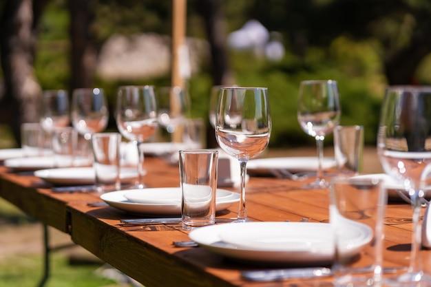 テーブルクロスのない木製のテーブルを用意しています。野外公園のカフェ