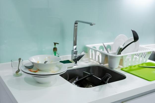 台所の流しの汚れた皿の山。家の中の混乱