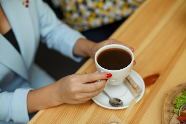 青いジャケットのトップビューの女性は、一杯のコーヒーを保持します。
