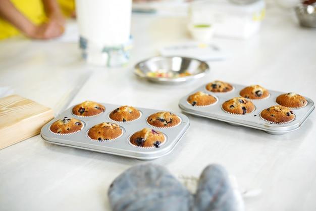 Кондитер вынул свежеиспеченные кексы в форму для выпечки на столе из духовки
