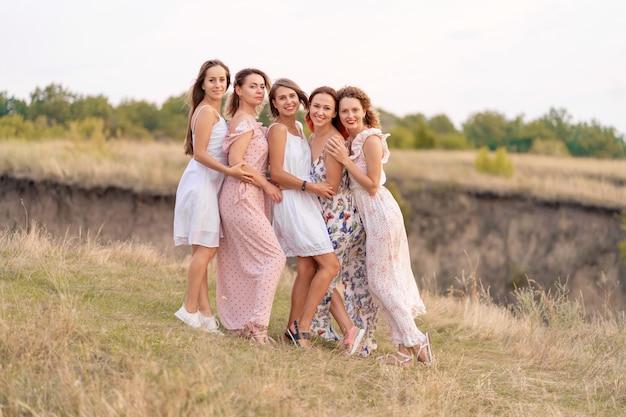 Веселая компания друзей-женщин наслаждается компанией и веселится вместе в живописном месте зеленых холмов.