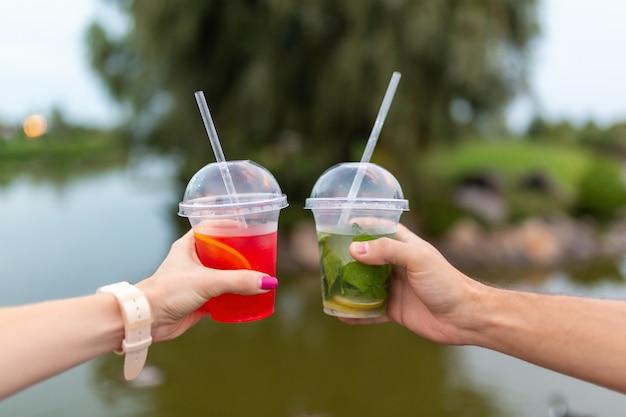 散歩中に男女が新鮮な飲み物を手に保持します。