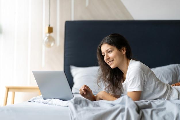 Молодая брюнетка женщина с ноутбуком, лежа на кровати. стильный современный интерьер. уютное рабочее место. покупки в интернете.