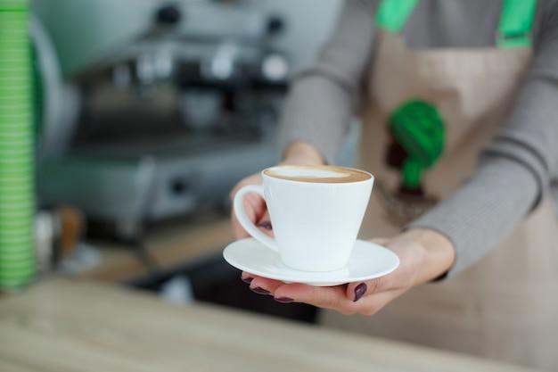 Бариста в фартуке в кафе дает клиенту только что сваренный свежий кофе