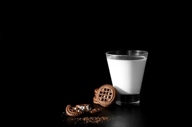 黒い背景にミルクとチョコレートクッキーのガラス