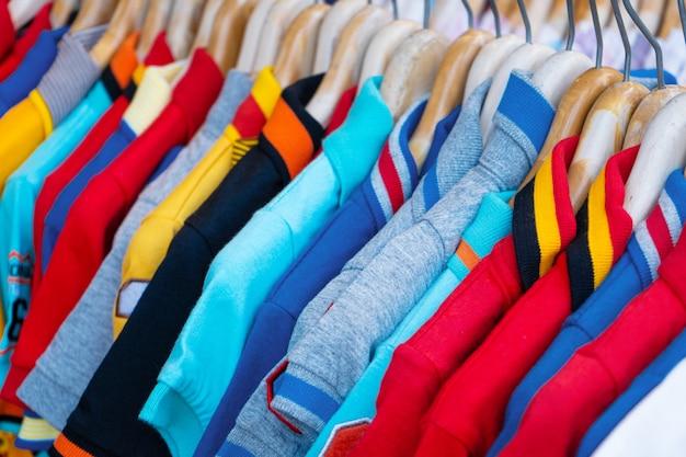 Разноцветные футболки на вешалке. магазин одежды