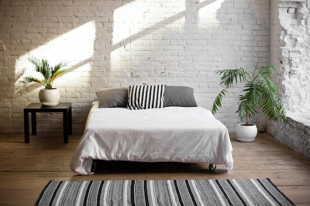 ベッドの近くに生きている花を持つシンプルでモダンな寝室のインテリア