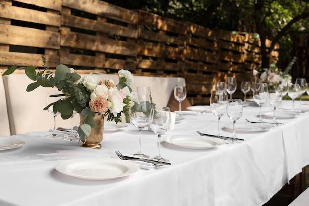 真ちゅう製の花瓶に生花で飾られた結婚式のテーブルセッティング。