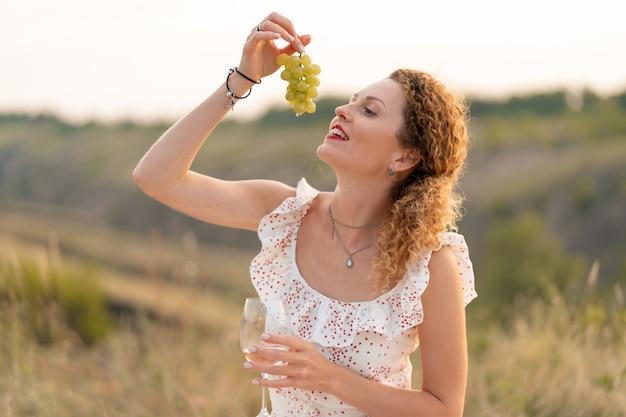 白いサンドレスの美しい若い赤毛の優しい少女は、ブドウを食べ、自然にワインを飲みます。