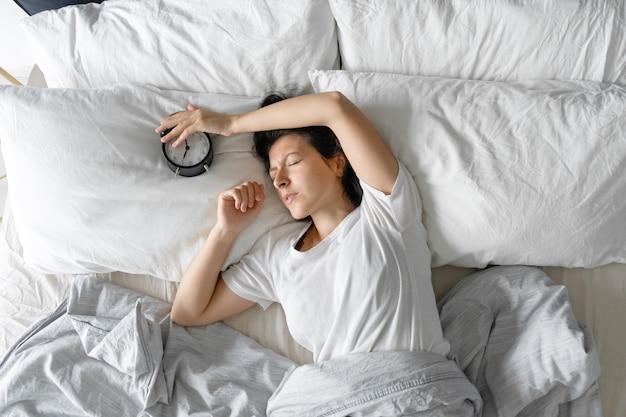 上からの眺め。女の子は目覚まし時計の隣で寝ます。睡眠を妨げる鳴っている目覚まし時計をオフにしようとしています。起きる時間。深い眠り。