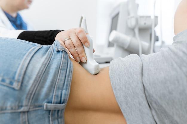 Врач крупным планом проводит ультразвуковую диагностику брюшной полости и внутренних органов пациента.