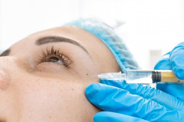 Косметолог делает уколы красоты в кожу молодой красивой женщины