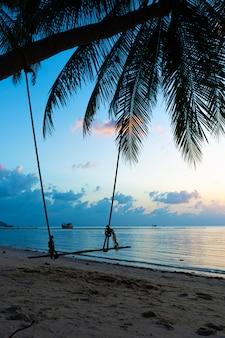 海沿いの熱帯の砂浜のビーチでヤシの木にぶら下がっているスイング
