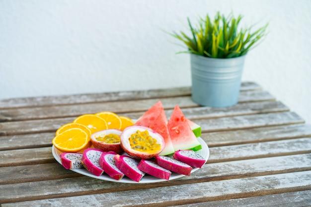スライスしたフルーツの白いプレート。新鮮な果物とビタミン。静物色の夏の果物。