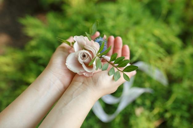 女性は新鮮なピンクのバラから作られた花嫁介添人のブレスレットを保持します。