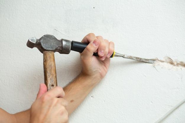 Ремонт помещений. мужчина делает канаву для прокладки кабеля в стене. прокладка электропроводки в стене.