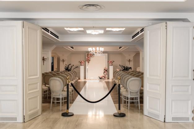 結婚式場。ゲスト用の白いお祝い椅子の列。新郎新婦の結婚式のアーチ。